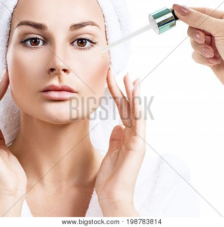 Cosmetic oil applying on face of young woman. Beauty therapy concept.