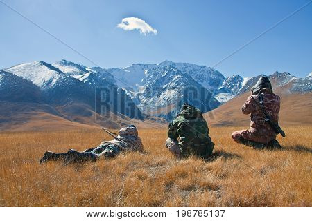 Three hunters looking through binoculars in mountains of Tien Shan. The Issyk-Kul region Kyrgyzstan