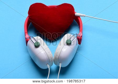 Leisure music and Valentines day concept. Modern and stylish earphones isolated on turquoise background. Headphones in white and red color with soft heart. Headset for music and heart shaped player