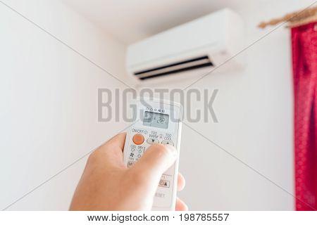 Hand Adjusting Temperature Of Home Air Conditioner
