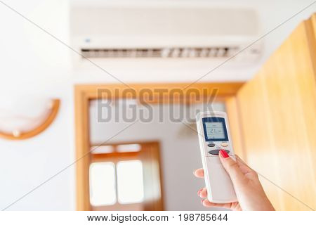 Close Up On Hand Adjusting Temperature Of Home Air Conditioner