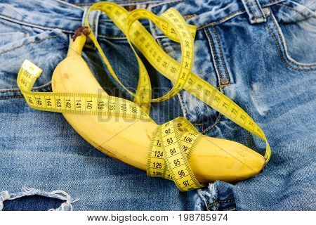 Banana wrapped with yellow measure tape on jeans selective focus. Mens denim pants with banana imitating male genitals. Health and male sexuality concept. Jeans loops zipper and pocket close up.