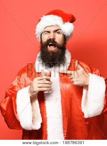 handsome bearded santa claus man with long beard on smiling face holding glass of alcoholic shot in christmas or xmas sweater and new year hat and shows on it on red studio background