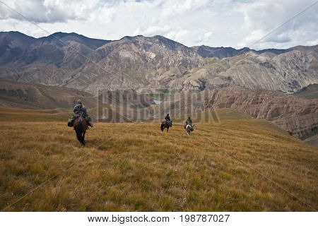 Hunters three horses returned with a trophy after a hunt in the mountains of Tien Shan Kyrgyzstan