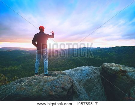Amateur Takes Photos With Phone On Peak Of Rock. Dreamy Landscape, Sun Hang On Horizon