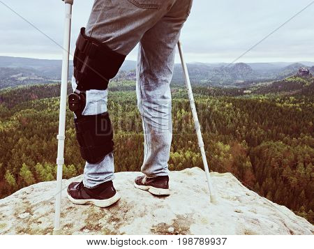 Man With Leg In Knee Cages And Crutches For Stabilization Stay On Rock. Hurt Tourist Walk In Mountai