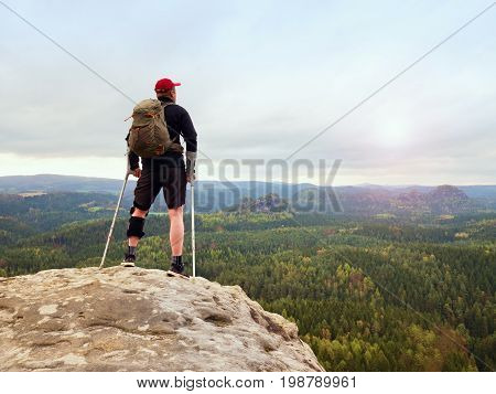 Happy Man Hiker Holding Medicine Crutch Above Head, Injured Knee Fixed In Knee Brace Feature