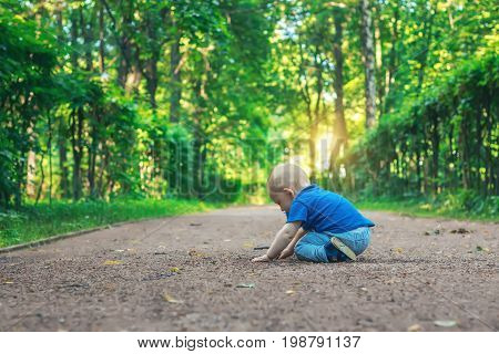 Small cute baby with nipple sits on the footpath in the dreamlike forest all alone. Little boy sitting on the ground and playing in the park. Beautiful nature background at sunset. Summer mood.