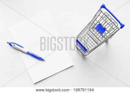 Cart from the grocery store and blank sheet of paper with pen on the white background. Shopping list. Empty shopping trolley. Business ideas and retail trade. Advertising of food products.