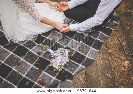 Enamored Bride And Groom Are Sitting On A Plaid Plaid Holding Hands. A Wedding Bouquet Nearby
