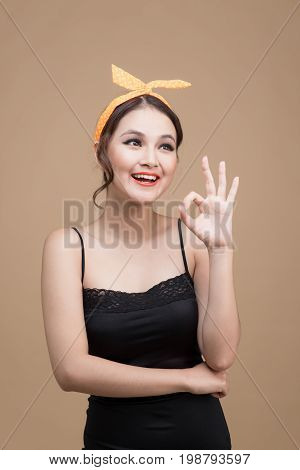 Portrait Of Asian Girl With Pretty Smile In Pinup Style With Hands Gesture On Yellow Background