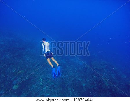 Freediver swims underwater in deep blue sea. Snorkeling man dives up to water surface. Open water diving lesson. Ocean deep open water view. Diver man silhouette undersea photo. Sea landscape view