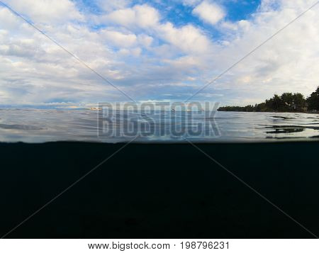 Double landscape with sea and sky. Above and below waterline in tropical seashore. Dark seawater and sunny sky. Sunset on beach. Exotic island shore view. Marine background. Tropical seaside banner