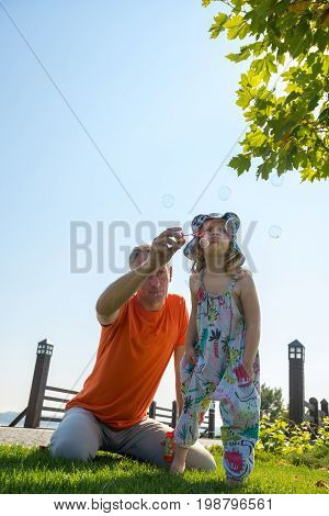 Focused Little Girl And Her Father Are Blowing Soap Bubbles