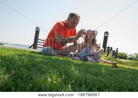 Little Girl And Her Smiling Father Enthusiastically Blowing Bubbles