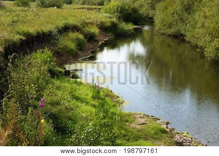 River coast with green grass. Russian nature.