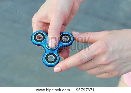 girl playing blue metal spinner in hands on the street female hands holding popular fidget spinner toy on gray background anxiety relief toy anti stress and relaxation fidgets