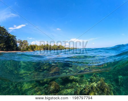 Split landscape with sea and sky. Split photo with tropical island and underwater coral reef. Clear blue sky and seawater. Above and below waterline sea view. Exotic seashore panorama. Split seascape