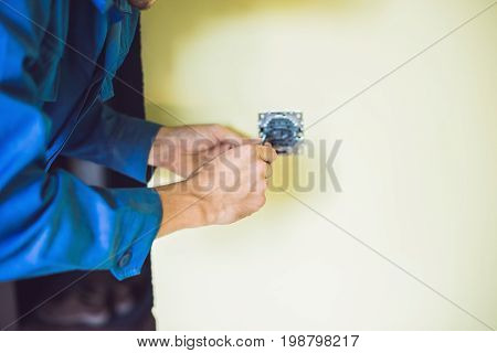 A Young Electrician Installing An Electrical Switch In A New House