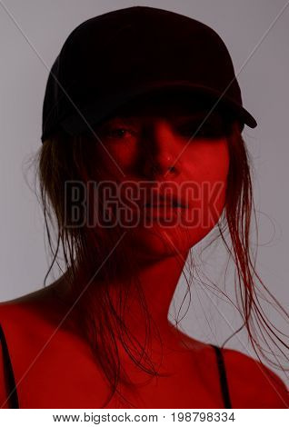portrait of happy young woman posing in underwear jeans and black baseball cap on against gray background