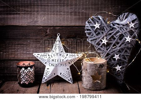 Christmas star heart candleholder and fairy light on aged wooden background. Decorative christmas composition. Selective focus.