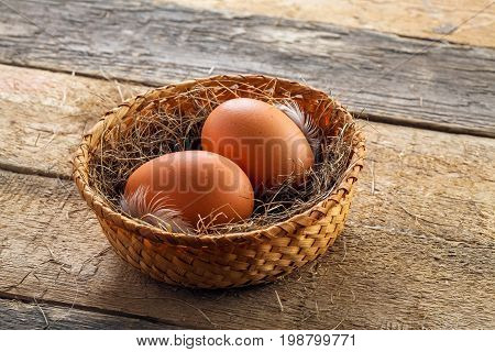 Two fresh farm eggs in a basket with hey and feather on a wooden table. Close-up shot.