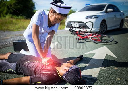 Female Nurse Helping Emergency Crp On Bicycle Man In An Accident