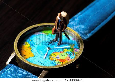 Old man on travel watches. World map travel photo banner. Aged traveler figurine. Retired backpacker travel. World time zones. Travelling around world concept. Senior age travel. Jet lag concept photo
