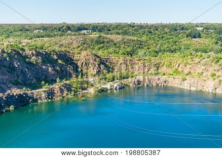 Ukraine Migea lake on the site of the former granite quarry. Steel cables trolley Zipline route over the lake. Zipline xtreme and active rest.