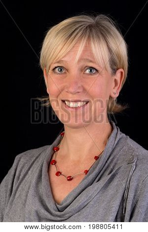 beautiful caucasian mature woman in gray top  - photograph on black background