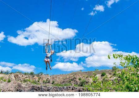 Ukraine Migea - July 30 2017: Zipline. A view of a child sliding on a steel cable against a beautiful blue sky with white clouds. Extreme and active rest.