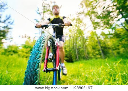 young man riding his mountain bike, focus on wheel
