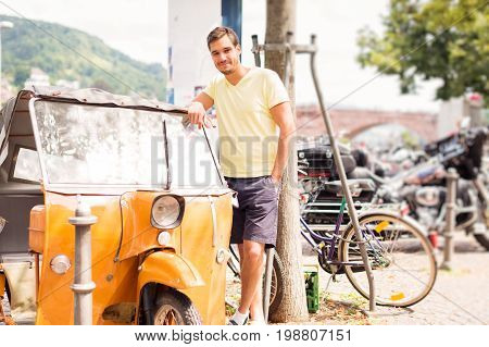 young man standing next to his old motorcycle