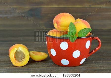 Apricots in the enamel cup on wooden background