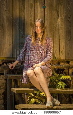 Vintage retro old fashioned female in dress sitting on stairs. Beauty and fashion concepts.