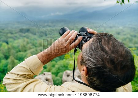 adult male forester examines the forest from the top of the mountain through binoculars. Hands and binoculars close-up.