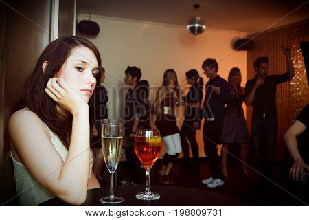 young sad woman is sitting alone in a nightclub while a crowd of people is dancing in the background. two drinks are standing on the table in front of her.