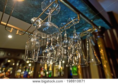 Luxury wine and champagne glasses hanging up side down in the pub