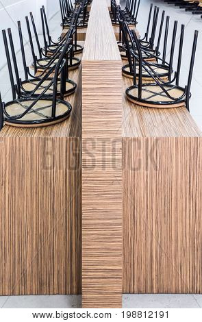 Metal chair row over the wooden table for keep after the restaurant closed.