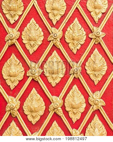Golden stucco pattern in the traditional Thail style on the red wall of the churchThailand.(Public area not required Property Release)