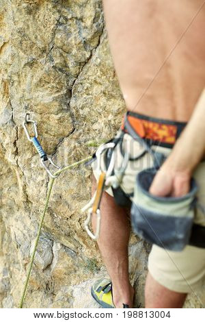 adult man rock climber. rock climber climbs on a rocky wall. harness and chalk bag close up, focus on the quickdraw