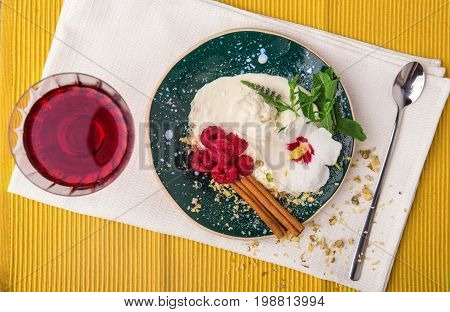 A view from above on a cold creamy snack.  A blue bowl of a milky ice cream, rustic raspberries, spicy mint and cinnamon. An icecream with a grape juice on a yellow fabric background.