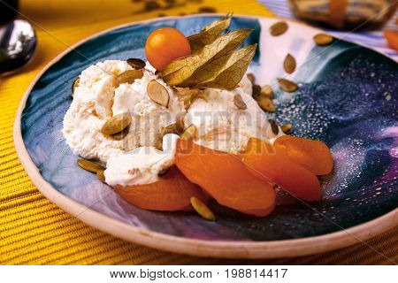 Close-up of a vanilla white ice-cream with apricots, pumpkin seeds and dried leaves on a yellow blurred background. Scoops of cold dessert full of nutritious vitamins. Cold and summer sweets.