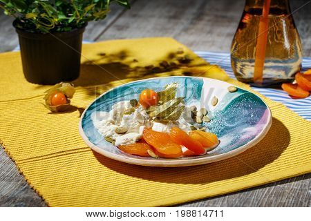 A cold ice cream with dried apricots, physalis and pumpkin seeds on a yellow cloth and on a wooden background. A glass of green tea with straw near the dessert. A pot with a green plant.