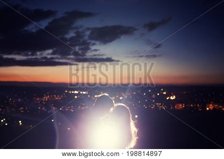 Lovers man and girl against background night city, night starry sky and horizon. Concept date Valentine's Day, first kiss love.