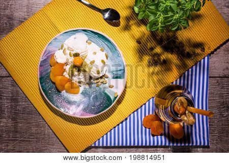 Cold and tasty vanilla ice cream with physalis, pumpkin seeds, and dried apricots on a yellow fabric and on a wooden background, top view. A little tea spoon near the dessert. A beverage on a striped cloth.