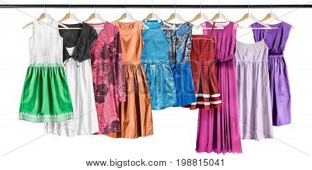 Group of dresses hanging on clothes racks on white background