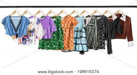 Set of shirts and tops hanging on clothes racks on white background