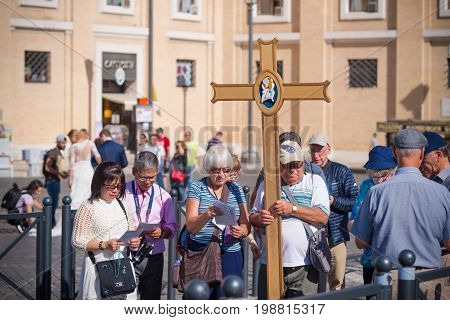 VATICAN CITY VATICAN - OCTOBER 16 2016: Group of unknown pilgrims carrying a cross in front of the saint peter's basilica