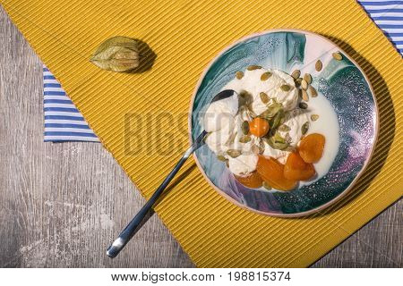 A fresh dessert with dried apricots, physalis on a yellow cloth and on a wooden background. Tasty ice cream with pumpkin seeds on a blue plate, top view. A tea spoon near the frozen yogurt.